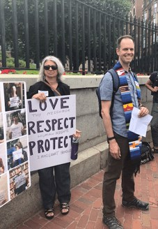 Cheryl and Nathan holding Love, Respect and Protect sign