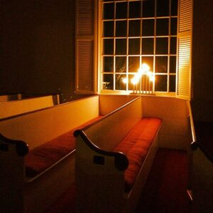 Empty pews with candles in window