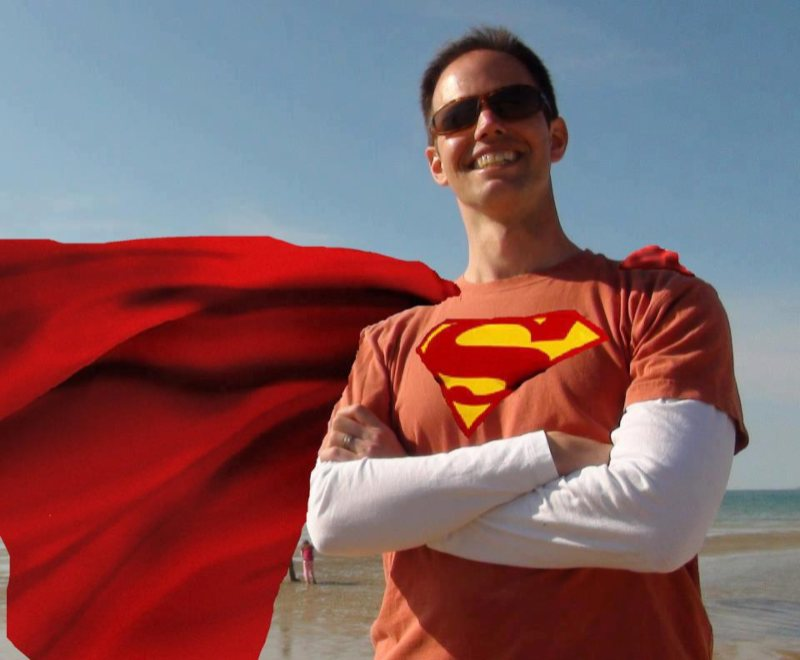 Rev Detering dressed in Superman costume at beach